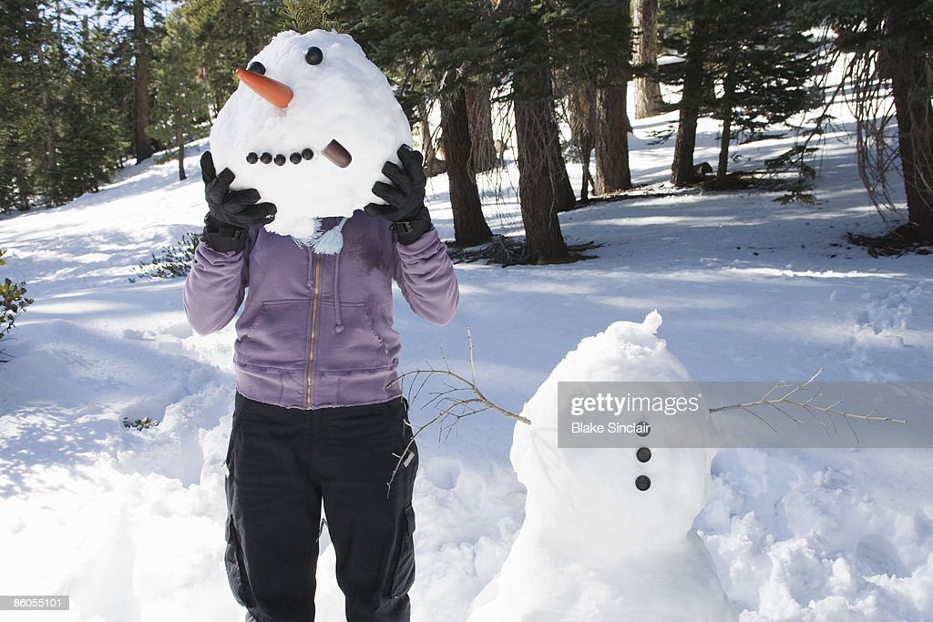 Woman holding snowman head in front of face : Foto de stock