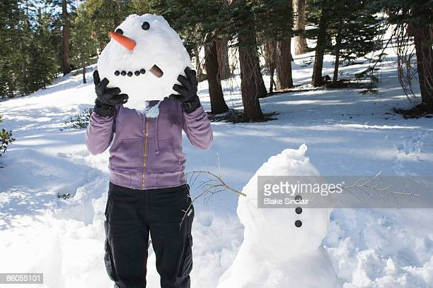 Woman holding snowman head in front of face