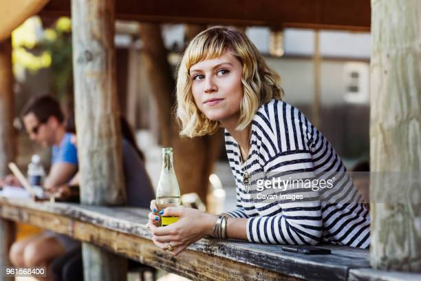 woman holding soda bottle while leaning on table in cafe - soda bottle stock photos and pictures