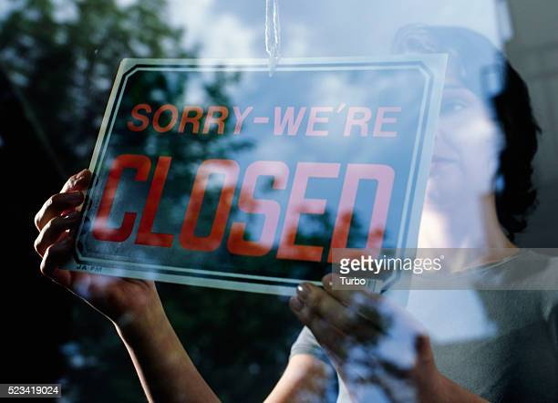 "woman holding ""sorry we're closed"" sign - closing stock pictures, royalty-free photos & images"