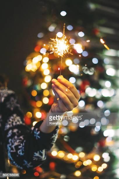 Frau mit Wunderkerze vor einem Weihnachtsbaum