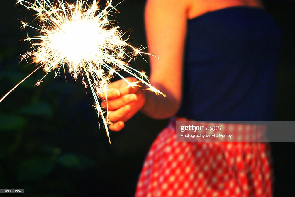 Woman holding sparkler : Stock Photo