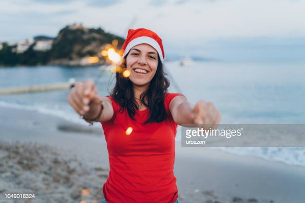 woman holding sparklers on the beach - hello december stock pictures, royalty-free photos & images