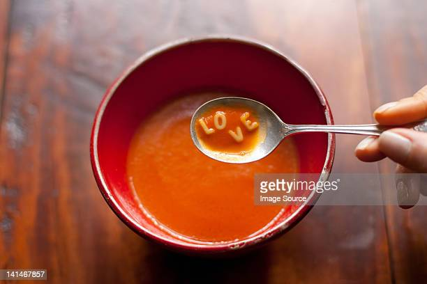 woman holding spoonful of soup with letters love - tomato soup stock photos and pictures