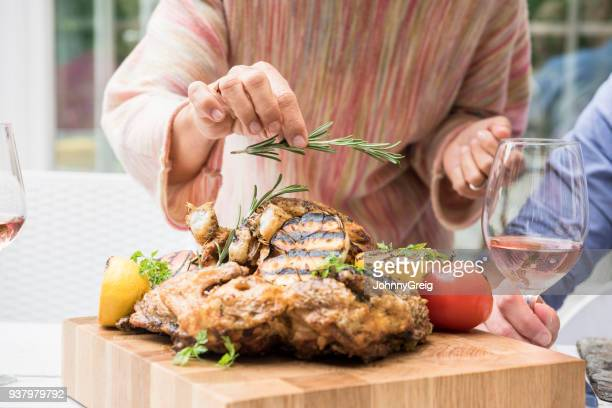 Woman holding sprig of rosemary and garnishing chicken