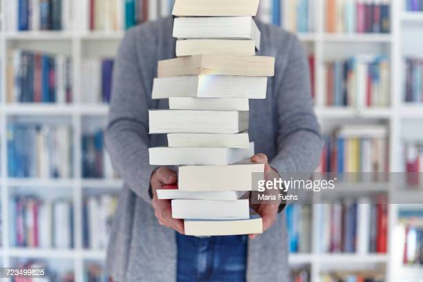 Woman holding stack of books, mid section