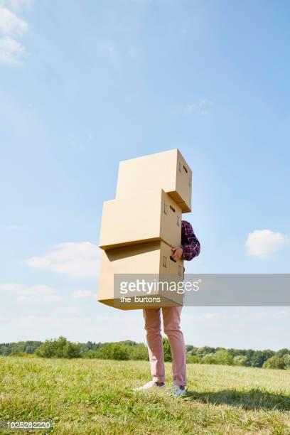 woman holding stack of cardboard boxes on a meadow against sky - einzelne frau über 30 stock-fotos und bilder
