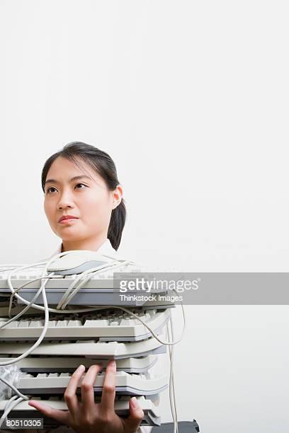 woman holding stack of computer keyboards - thinkstock stock-fotos und bilder