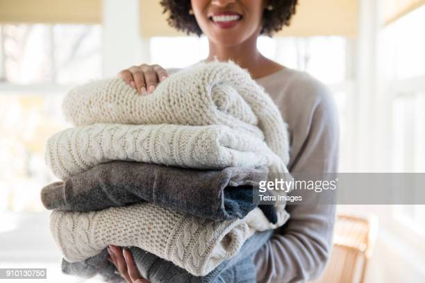 woman holding stack of folded sweaters - sweater stock pictures, royalty-free photos & images
