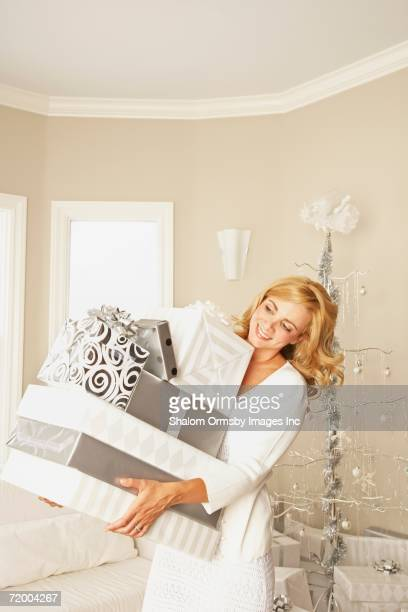 Woman holding stack of gifts on Christmas