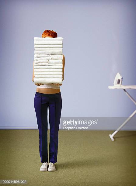 Woman holding stack of towels in front of face
