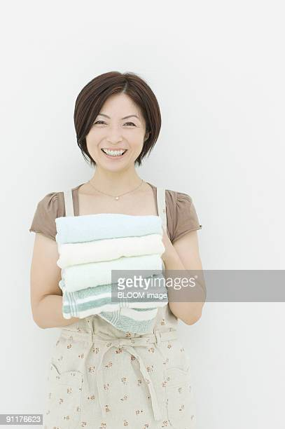 woman holding stack of towels - homemaker stock pictures, royalty-free photos & images