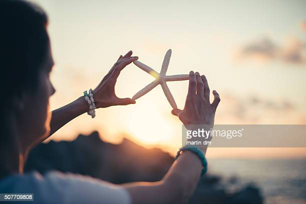 Woman holding starfish on sunset
