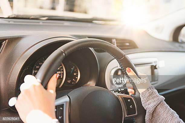 Mujer agarrando volante y conducción automóvil durante el día