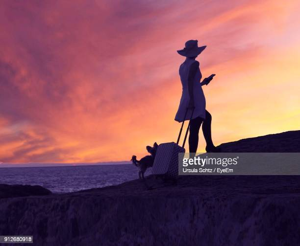 Woman Holding Suitcase By Dog Standing On Cliff At Beach Against Sky During Sunset