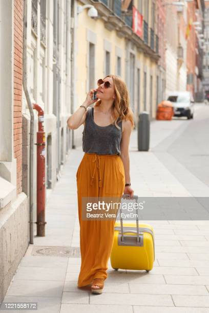 woman holding suitcase talking over smart phone while walking on sidewalk in city - public celebratory event stock pictures, royalty-free photos & images