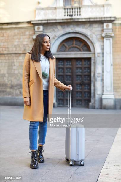 woman holding suitcase while standing on street - one young woman only stock pictures, royalty-free photos & images