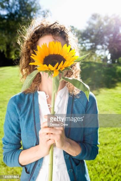 woman holding sunflower in front of her face - alleen één mid volwassen vrouw stockfoto's en -beelden