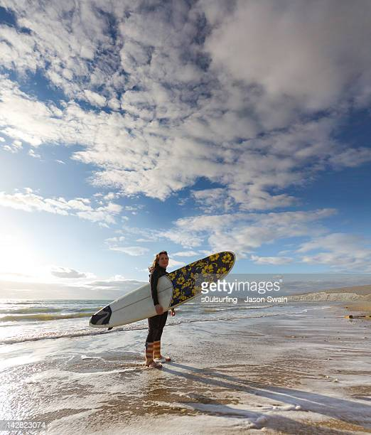 woman holding surf board at beach - compton bay isle of wight stock pictures, royalty-free photos & images