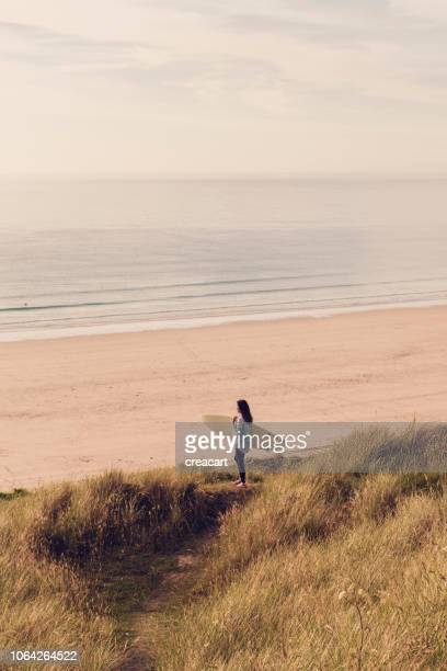 gwithian トーワン ビーチ、コーンウォール、6 月の日に日没近くを見渡してサーフボードを持った女性。 - グイチアン ストックフォトと画像