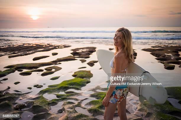 Woman holding surfboard, walking towards sea, Balangan, Bali, Indonesia