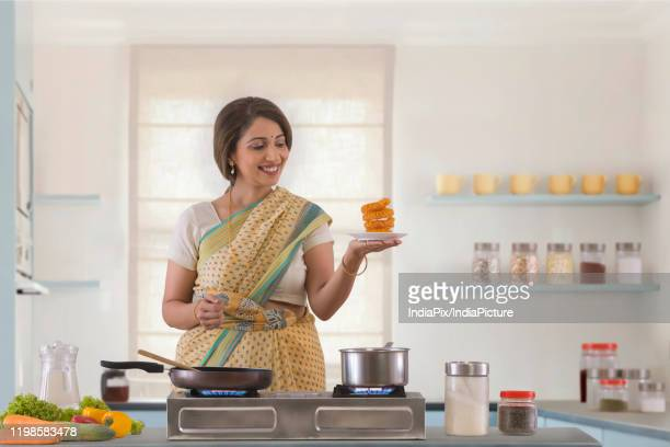 woman holding sweet dish in kitchen - sweet food stock pictures, royalty-free photos & images