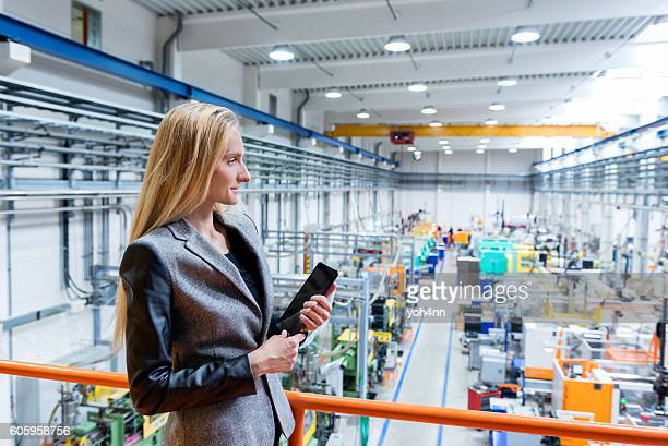 Woman holding tablet on top of a new factory