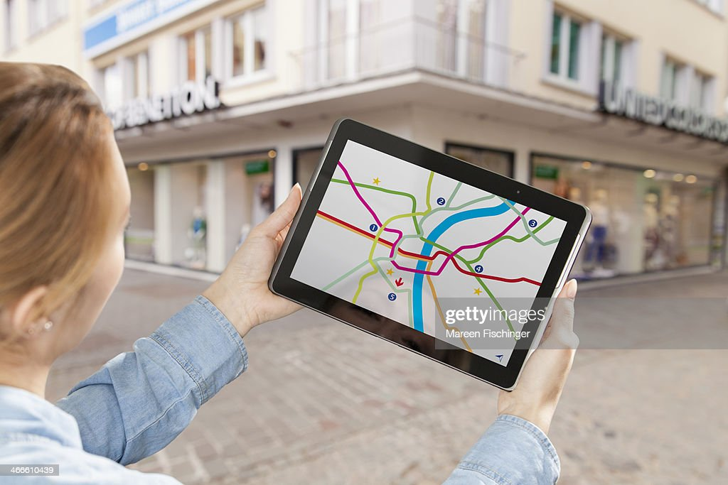 Woman holding tablet with map app in city : Stock Photo