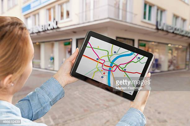 Woman holding tablet with map app in city