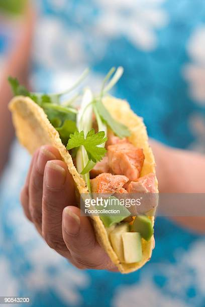 Woman holding taco, mid section