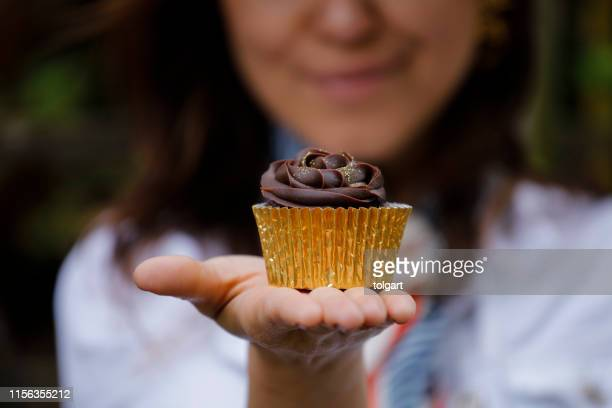 woman holding tasty chocolate cupcake - hand stock pictures, royalty-free photos & images