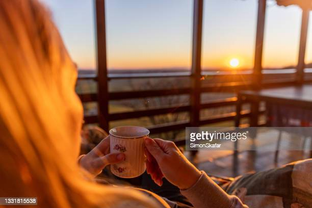 woman holding tea cup and enjoying sunset - moment of silence stock pictures, royalty-free photos & images