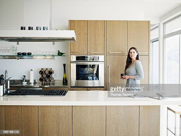 Woman holding tea in kitchen of contemporary home