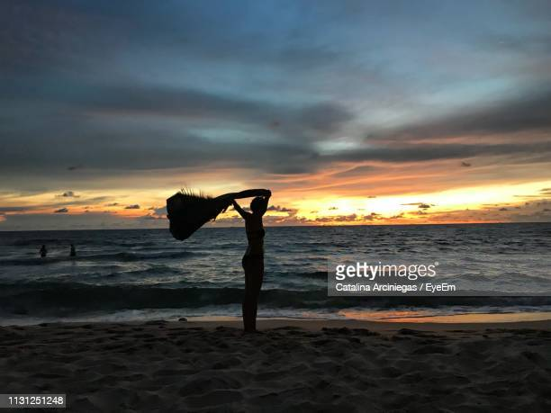 woman holding textile while standing at beach against sky during sunset - pretty vietnamese women stock pictures, royalty-free photos & images