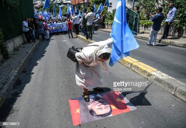A woman holding the flag of East Turkestan spits on a poster of Chinese President Xi Jinping during a protest of supporters of the mostly Muslim...