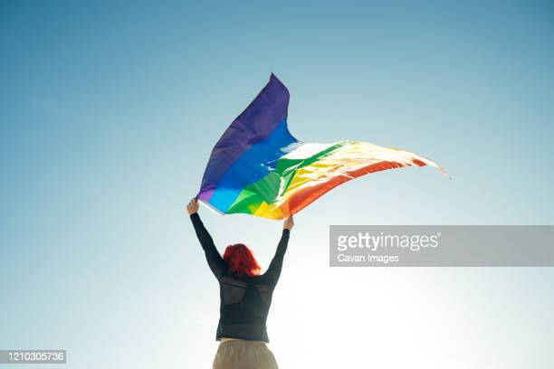 woman holding the gay rainbow flag on blue sky background. happiness, freedom and love concept for same sex couples. -  lgbtqi ストックフォトと画像