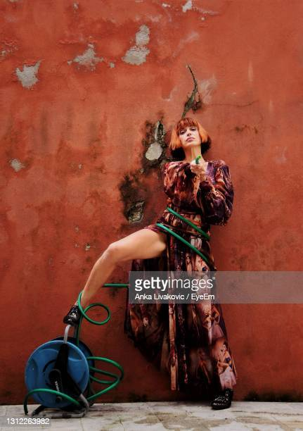 woman holding the rubber for watering against orange wall - rubber dress stock pictures, royalty-free photos & images