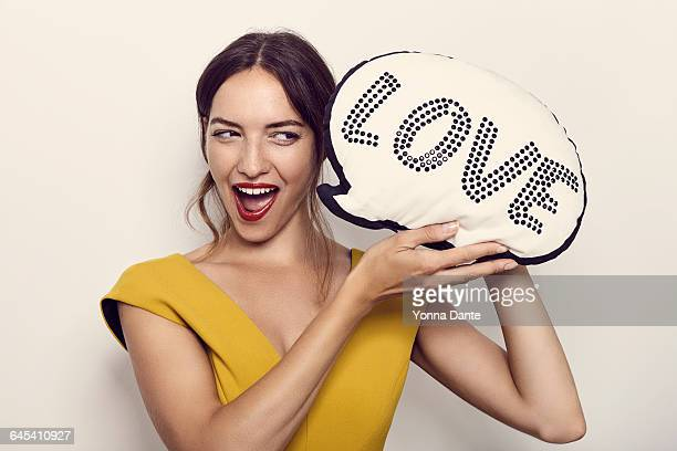 woman holding thought-balloon shaped cushion