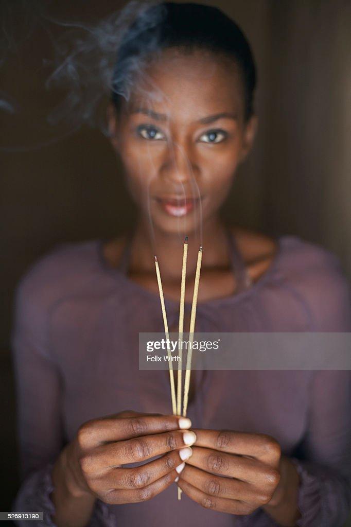 Woman holding three sticks of incense : Stock-Foto