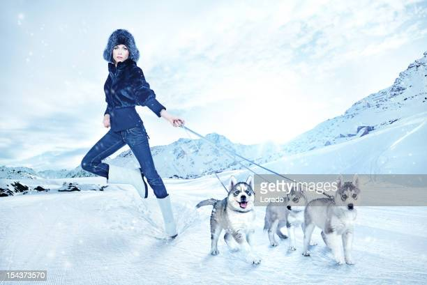 woman holding three young huskies against mountain background