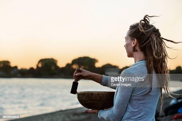 woman holding tibetan singing bowl at beach during sunset - tibetaanse cultuur stockfoto's en -beelden