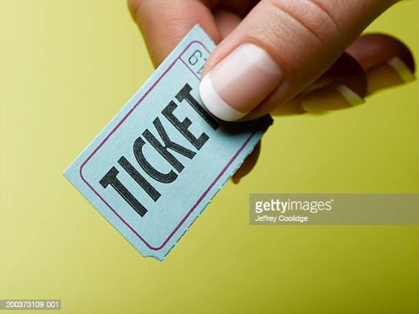 Woman holding ticket stub, close-up