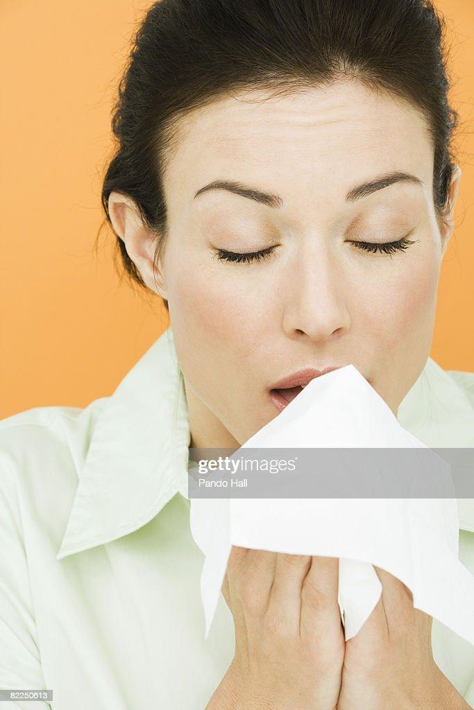 Woman holding tissue, eyes closed : Stock Photo