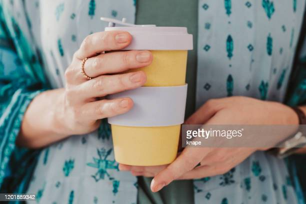 woman holding to go take out coffee cup - reusable stock pictures, royalty-free photos & images