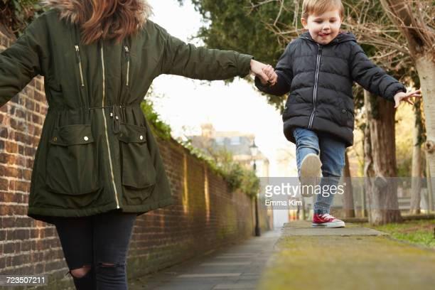 woman holding toddler sons hand walking on street wall - emma white stockfoto's en -beelden