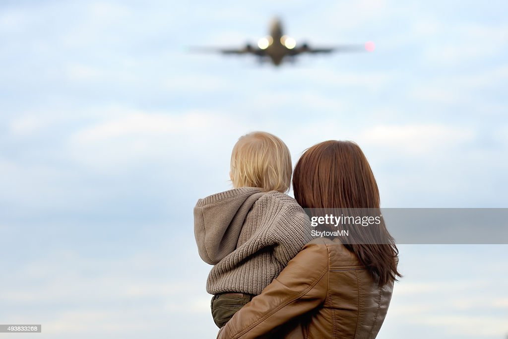 Woman holding toddler with airplane on background : Stock Photo