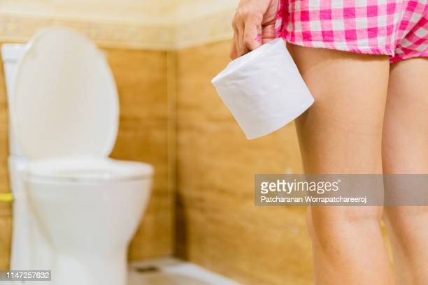 woman holding toilet tissue roll in front of toilet bowl. health and cleanliness concept - femme wc photos et images de collection