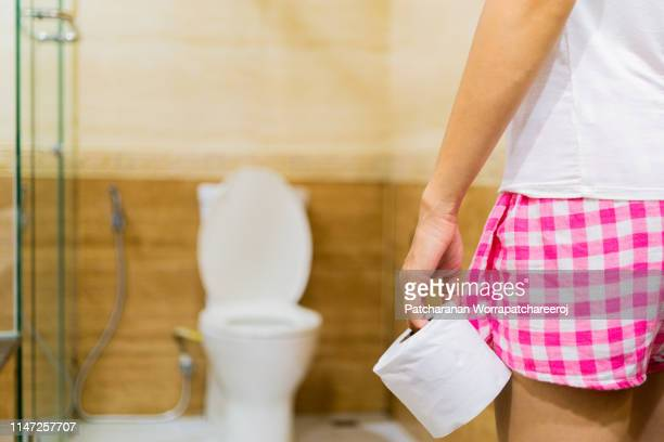 woman holding toilet tissue roll in front of toilet bowl. health and cleanliness concept - 下痢 ストックフォトと画像