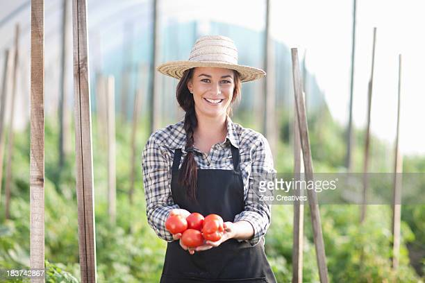 Woman holding tomatoes grown at farm