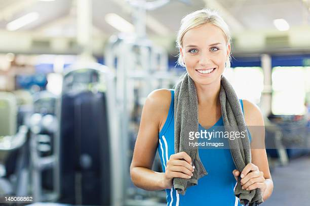 Woman holding towel around neck in gym